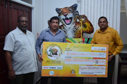 Senior Manager of Guyana Beverage Inc., Shawn Hera (center) presents a $500,000 cheque to Guyana Tourism Authority's Director, Indranauth Haralsingh (right) and Permanent Secretary to the Ministry of Public Telecommunications, Derrick Cummings (left)