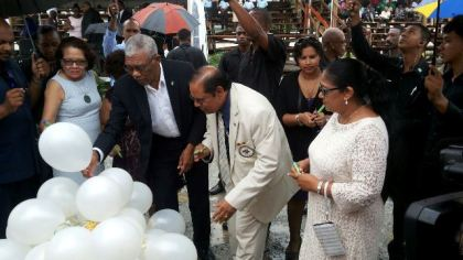 President David Granger and Prime Minister Moses Nagamootoo and their spouses write messages of unity and peace on while balloons