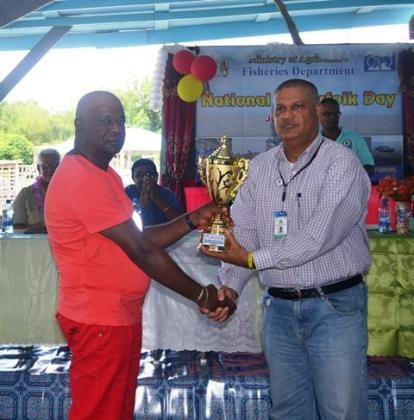 Region 6's Special Assistant to the Prime Minister, Mr Gobin Harbhajan handing over a trophy to one of the participants in the day's activities.