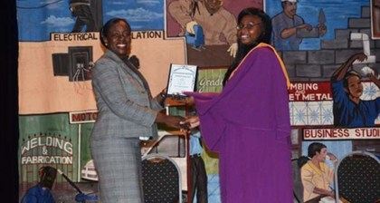 Minister within the Ministry of Education, Nicolette Henry presents plaque to best graduating YEST student of Vryman's Erven training centre, Shaquilla Sharpe