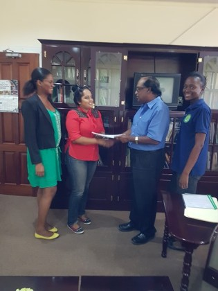 Chief Executive Officer of NAREI, Dr. Oudho Homenauth presents a copy of the contract to a representative of S&K Construction Services. Also in the picture are head of the Mangroves Department Kene Moseley and NAREI's Engineer Luandra Jack