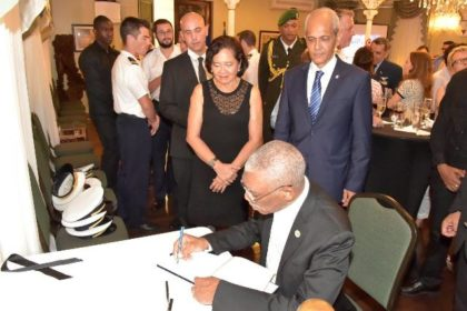 President David Granger signs the Book of Condolences, which was opened at the Reception in observance of France's National Day, for the victims of the terrorist attack in Nice. First Lady, Mrs. Sandra Granger and France's Ambassador to Guyana, Mr. Michael Prom look on.
