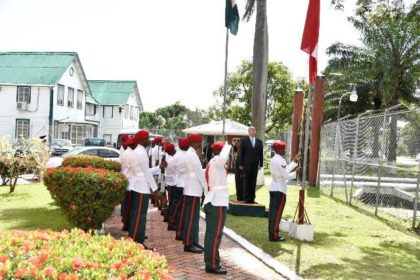 Ambassador Christensen stands at attention as members of the Guyana Defence Force hoist the National Flags of the two countries