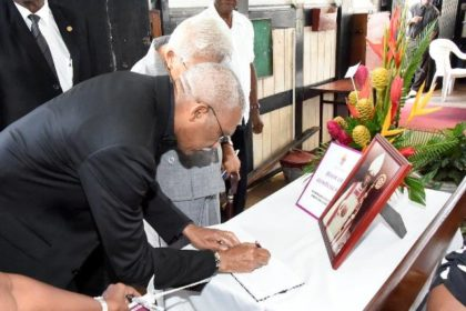 President David Granger signs the Book of Condolences for the late Bishop Randolph George at his funeral service, held at the St. George's Cathedral