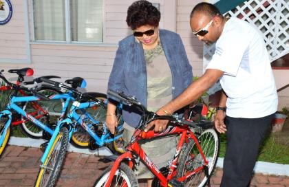 Mr. Deavindra Jagroo points out a particular feature on one of the bicycles to Minister of Social Cohesion, Ms. Amna Ally, this morning, at the Ministry of the Presidency