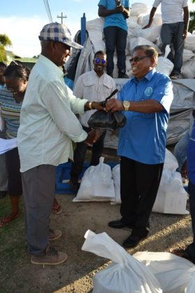 Mr. Rajkumar Suhkra and CDC Chairman Colonel (ret'd) Chabilall Ramsarup share a light joke as he collects his hamper at the Union/Naarstigheid Neighbourhood Democratic Council at Bush Lot.
