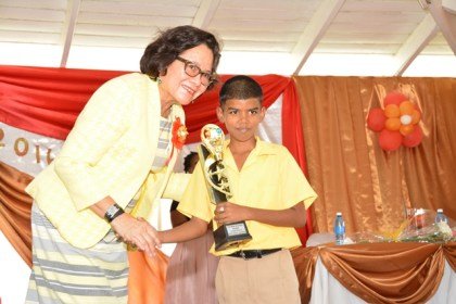 Master Alex Ms. Alex Doodnauth smiles shyly after First Lady, Mrs. Sandra Granger presented him with the trophy for the Most Improved Student