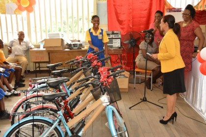 Ms. Jada Leitch laughs with joy after Ms. Pamela Nauth, Technical Officer at the Ministry of Social Cohesion invites her to choose her bicycle. Several of the Grade Six teachers (pictured right) cheer her on.