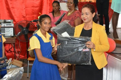 Ms. Varisty Raywat receives her backpack from Ms. Pamela Nauth, Technical Officer from the Ministry of Social Cohesion