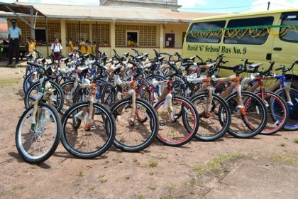 Twenty-five bicycles and the 'David G School Bus No. 9' in the compound of the Mahdia community centre