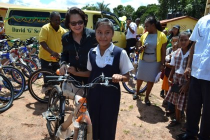 First Lady, Mrs. Sandra Granger encourages a shy Ms. Shonette Andrews to display her bicycle, in the community Centre compound, Mahdia, while businessman Mr. Roger Hinds, (left, background) readies another bicycle for the First Lady.