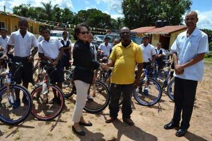First Lady, Mrs. Sandra Granger and Mahdia businessman, Mr. Roger Hinds shake hands as Regional Executive Officer, Mr. Rafel Downes and some of the recipients of spanking new bikes look on.