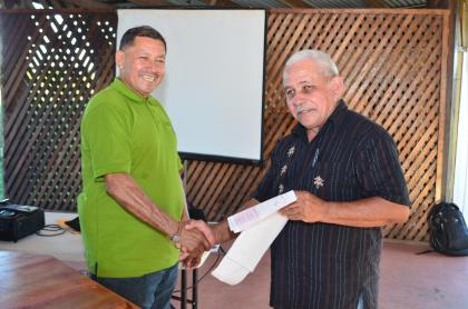 Minister of Indigenous Peoples' Affairs, Sydney Allicock handing over a Jubilee grant cheque to another toshao
