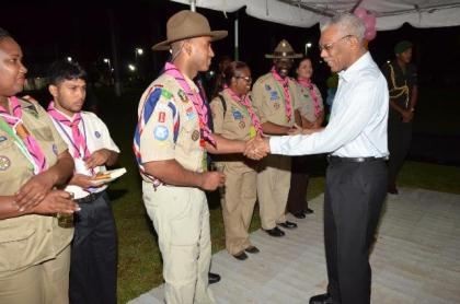 President David Granger shares a light moment with this team leader from Aruba at the reception, which was hosted on the lawns of State House, earlier this evening