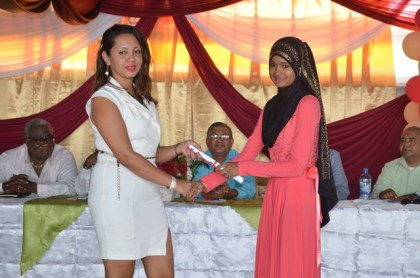 Trainer Ishranie Singh presenting a certificate to best student in Information Technology, Shazeema Nizamudin at the National Training Project for Youth Empowerment graduation ceremony at the Upper Corentyne Industrial Training Center