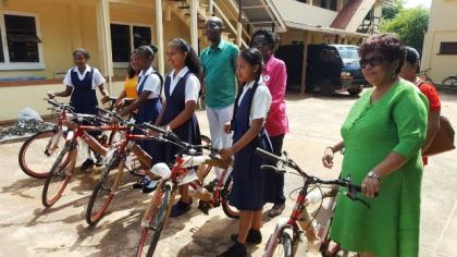 Minister of Social Cohesion Amna Ally and the top NGSA students of Region Nine with their bicycles
