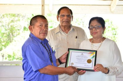 NRDDB Vice Chair Michael Williams receives the OPM Certificate of Recognition from Mrs Sita Nagamootoo while Prime Minister Moses Nagamootoo looks on.