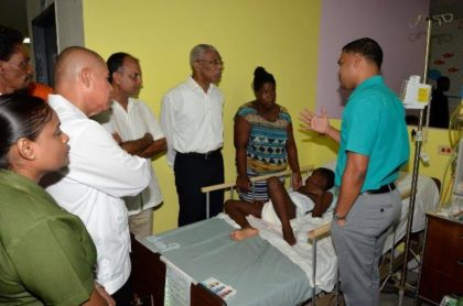 President David Granger receiving an update on Nick Josh Omari Joseph's condition from Dr. Amarnauth Dukhi at the Georgetown Public Hospital Corporation. Joseph's mother, Ms. Delia Finistere is standing at the President's left and Minister of Public Health, Dr. George Norton is at second from left