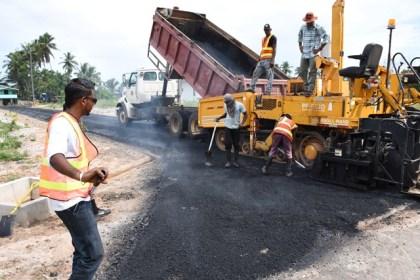 Contractors applying asphalt on a road in Mackenzie, Linden