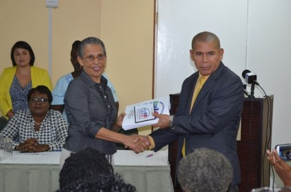 Minister of Public Health, Dr. George Norton (Right) receives the final report on the assessment of hospitals working towards Baby Friendly Hospital Status from Lead Consultant, Paula Trotter