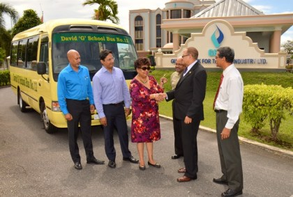 "Minister Ally happily receives the key from Mr. Robin Stoby, Chairman of GBTI to the ""David G"" school bus, which was donated to President Granger Five Bs initiative by the Guyana Bank for Trade and Industry Ltd (GBTI) as the directors look on (L – R) Mr. Suresh Beharry, Director of GBTI and Edward B. Beharry Company, Mr. Anand Beharry Director of GBTI and Edward B. Beharry Company, Mr. Basil Mahadeo, Director of GBTI and Mr. John Tracey the Chief Executive Officer of GBTI."