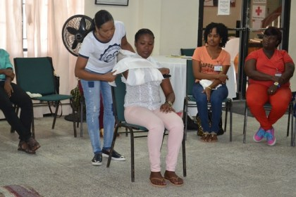 "Two participants, demonstrate First Aid response for a broken arm by ""Sling and a binder"""