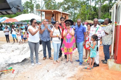 Minister of Social Cohesion Amna Ally, Minister within the Ministry of Public Infrastructure, Annette Ferguson and owner of ACS, Peter Lewis and regional and municipal officials help a young girl cut the ribbon to officially commission the asphalt plant in Bartica