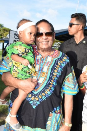 Prime Minister Moses Nagamootoo poses with a child dressed in her traditional African attire