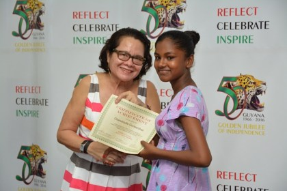 First Lady, Mrs. Sandra Granger presents a Certificate of Achievement to Miss Chandroutie Gooberdhan, one of the graduates from the workshop held at the Lusignan-good Hope Learning Centre, Lusignan, East Coast Demerara.