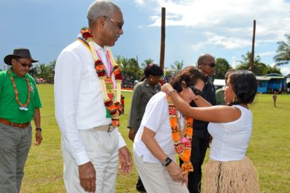 First Lady Mrs. Sandra Granger is garlanded by this young lady from Kamarang as President David Granger looks on.