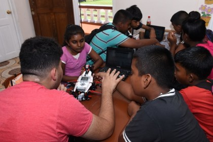 Volunteer, Sony, assisting the children with building a robot