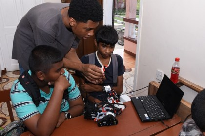 Caleb Christian demonstrating to the children how to build the robot