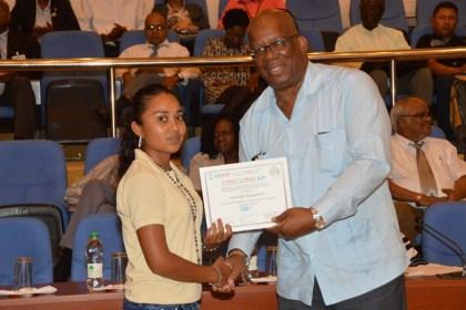 Ms. Christina Ramdeholl receiving her certificate from Finance Minister, Mr. Winston Jordan