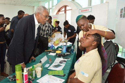 President David Granger carefully observes this young beautician's technique at one of the booths set up at the Arthur Chung Convention Centre