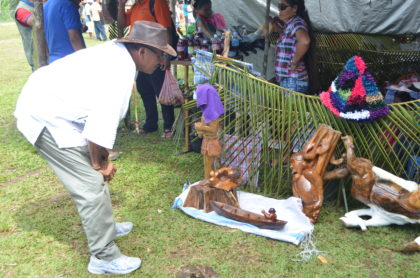 Minister of Indigenous Peoples' Affairs, Sydney Allicock examining some of the items on display at the Moruca expo 2016