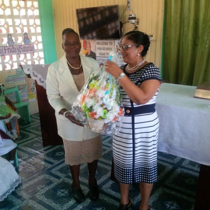 Mrs. Sita Nagamootoo is presented with a bouquet