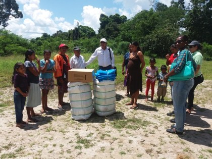Minister Norton hands over the medication, treated mosquito nets and clothing to residents of Kurutuku