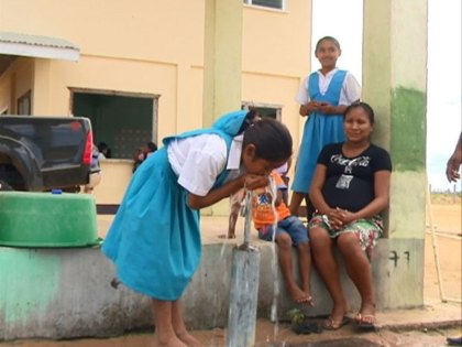 A schoolgirl drinking water at a standpipe at a school in Region Nine
