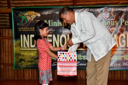 Minister of Indigenous People's Affairs, Mr. Sydney Allicock presenting a token to a young lady representing the Baha'i community