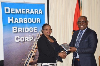 General Manager, DHBC, Rawlston Adams handing over a copy of the OS&H handbook to Minister of Social Protection, Volda Lawrence