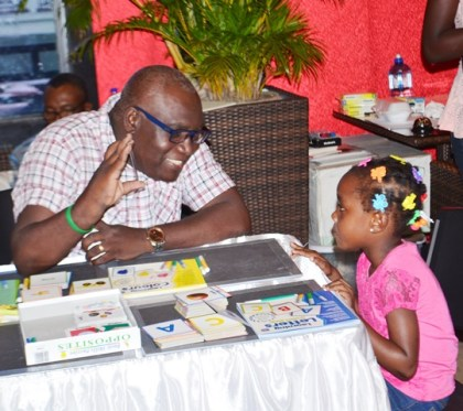 Marcel Hutson, Chief Education Officer (acting), Ministry of Education interacting with one of the participants at the literacy clinic held at Princess / Ramada Fun City