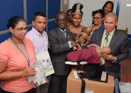 Minister of Public Health, Dr. George Norton receives donation of obstetrics equipment from PAHO/WHO Representative, Dr. Adu-Krow in the presence of Health officials