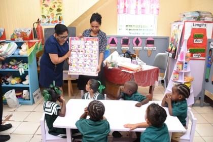 Mrs. Sita Nagamootoo teaching a child of Selman Fraser Nursery School the alphabet