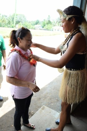 Minister in the Ministry of Communities, Dawn Hastings- Williams being garlanded by a young White Water resident upon her arrival to the village