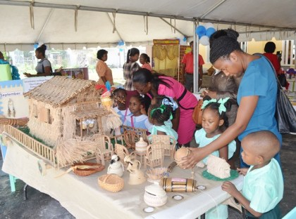 Children and teachers examining the corner displaying the indigenous culture at the exhibition to mark 40 years of development in Early Childhood/Nursery Education in Guyana