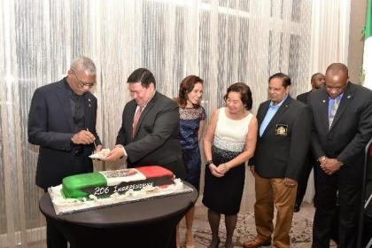President David Granger cuts the cake with Ambassador Ivan Roberto Sierra-Medel as part of the Independence celebrations. They are accompanied by First Lady, Mrs. Sandra Granger, Prime Minister, Mr. Moses Nagamootoo, Minister of State, Mr. Joseph Harmon and the Ambassador's wife Ms. Norma Alizia de la Torre Diaz
