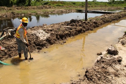 Contractors pumping water from part of the dam in 'E' Field, Sophia to complete road works