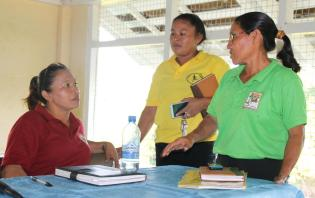 Minister within the Ministry of Communities Dawn Hastings-Williams interacting with two parents in Kwebanna, Region Seven
