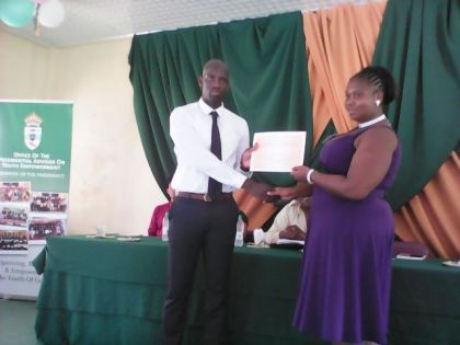 Mr. Ronald Austin Jr. presents certificate of participation to Ms. Latricia Bovell.