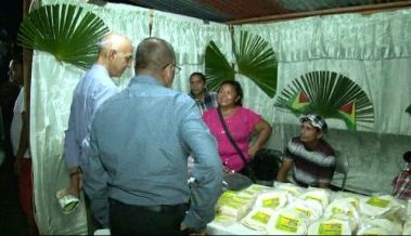 Minister of Communities Ronald Bulkan speaks with indigenous entrepreneurs at Essequibo Night 2016